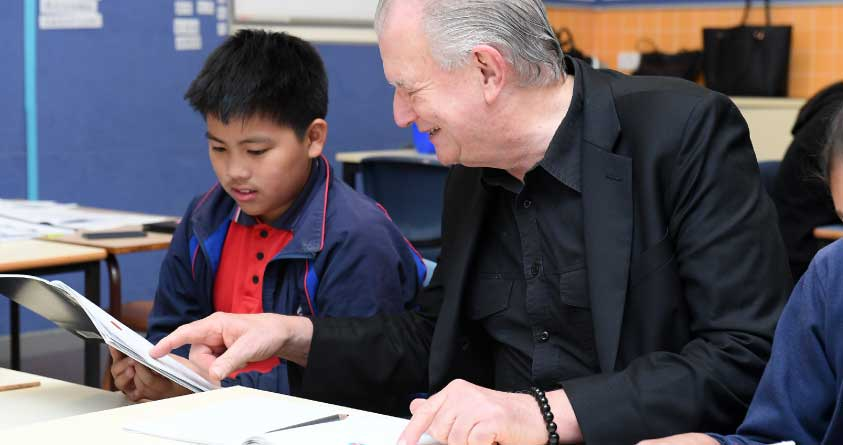 Rev. Bill Crews helps a child to read.